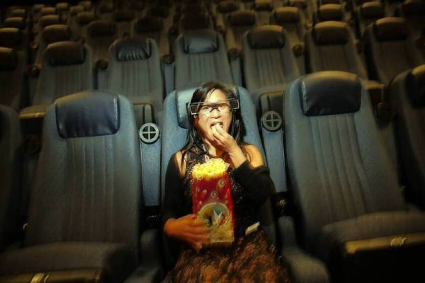 Lisa Yuan, who is hearing impared, wears a pair of Sony's glasses that show closed captions at Regal's theater at L.A. Live in downtown Los Angeles.