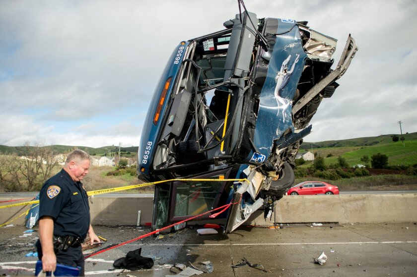 A California Highway Patrol officer moves belongings from a Greyhound bus crash that left two dead and at least eight injured on Tuesday, Jan. 19, 2016, in San Jose, Calif. A Greyhound spokeswoman said the bus, which left Los Angeles Monday night, was carrying 20 passengers in addition to the driver. (AP Photo/Noah Berger)