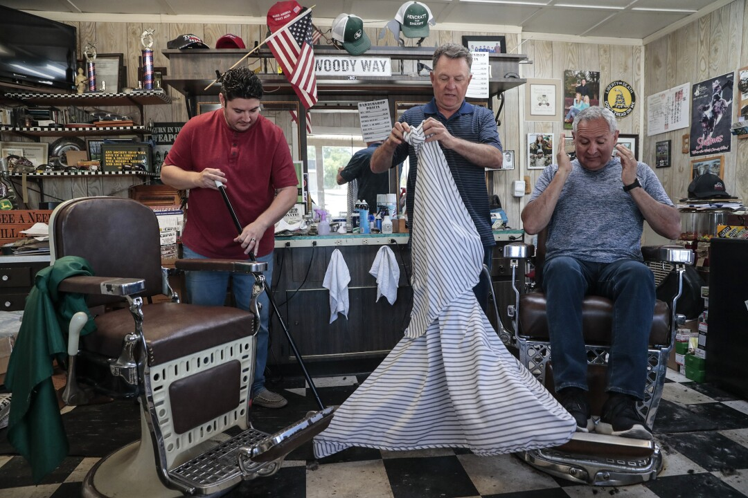 Barber Woody Clendenen, center, refused to close his business as COVID-19 spread throughout the state.