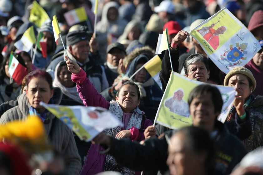 Pilgrims wave flags as they wait for the arrival of Pope Francis in Ecatepec, Mexico, Sunday, Feb. 14, 2016. Pope Francis will give a Mass at an outdoor field in the capital's suburb of Ecatepec to an estimated crowd of 400,000 pilgrims. It is to be his biggest event during his trip to Mexico. (AP