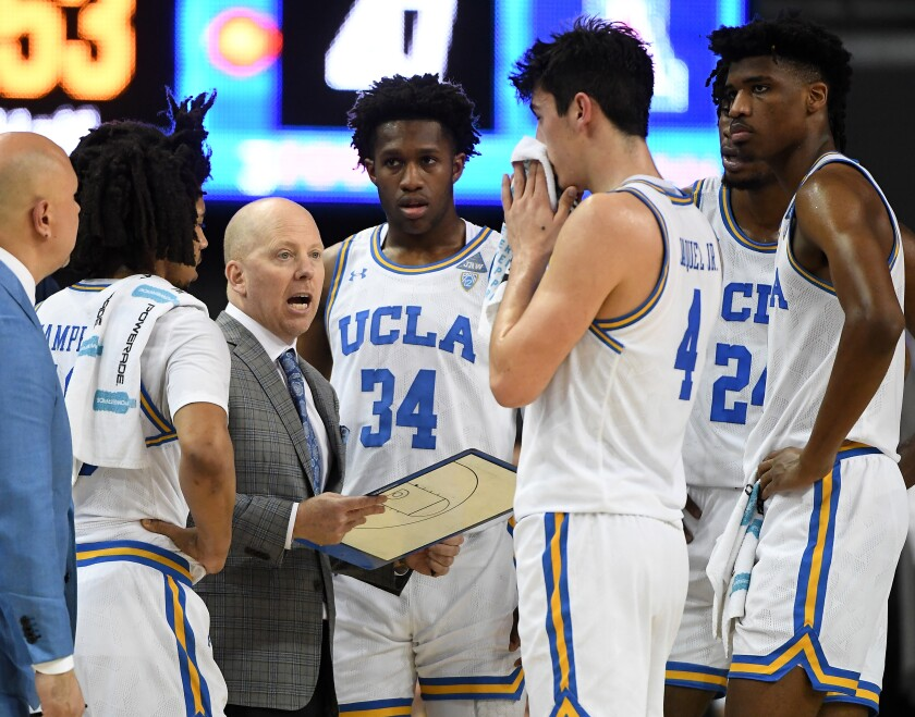 UCLA players Tyger Campbell (10), David Singleton (34), Jaime Jaquez Jr. (4), Jalen Hill (24) and Chris Smith (5) listen as head coach Mick Cronin talks during a timeout in the second half against Arizona at Pauley Pavilion on Saturday.