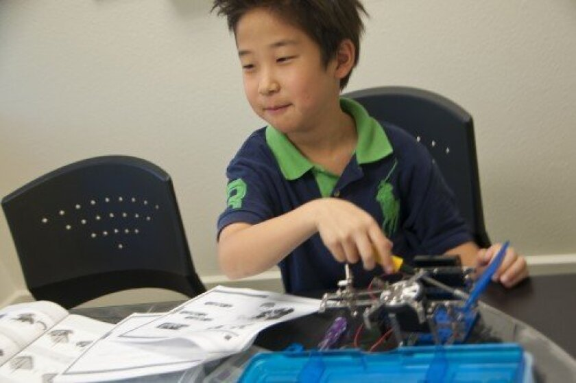 Bryan Yoo, a second-grader living in Carmel Valley, tests the movability functions of a robot he put together in a recent class at Robolink. Photo/Claire Harlin