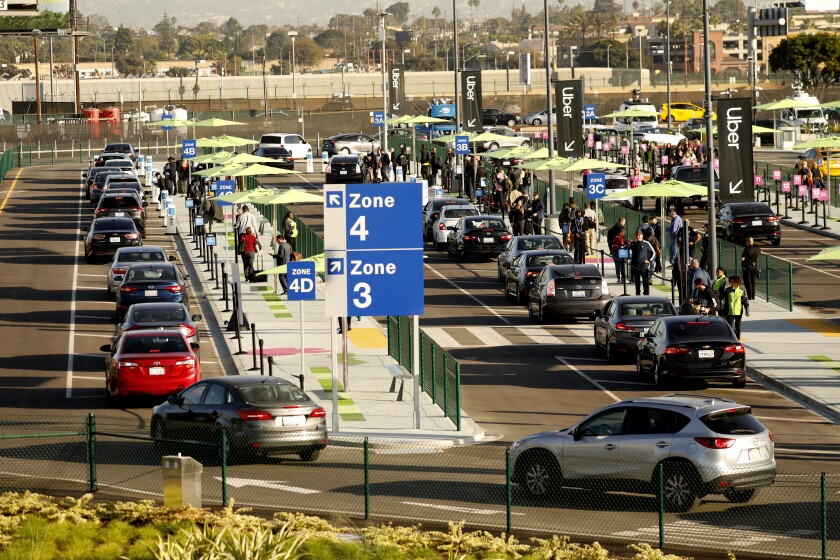 Travelers wait for Uber, Lyft and taxi pickups at the new pickup lot at LAX