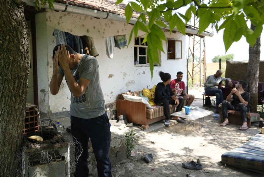 Migrants rest in front of an abandoned house in the village of Majdan, Serbia, Thursday, July 22, 2021. Empty or abandoned houses serve as temporary homes to people who fled their own homes in the Middle East, Africa or Asia with an aim to start a new life somewhere else. (AP Photo/Darko Vojinovic)