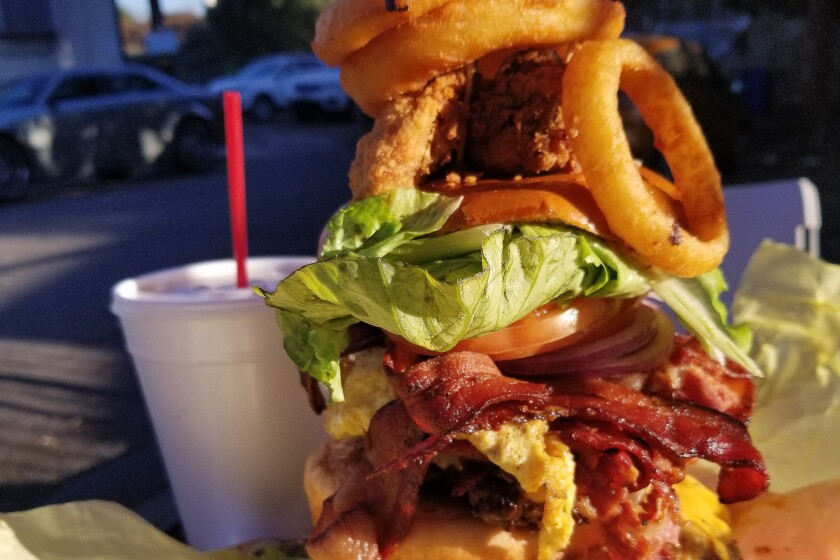 The Leaning Tower of Watts burger at Hawkins House of Burgers: Three ground beef patties, bacon, a chicken wing, a couple of fried eggs, melted cheese, lettuce, tomato and onion rings.