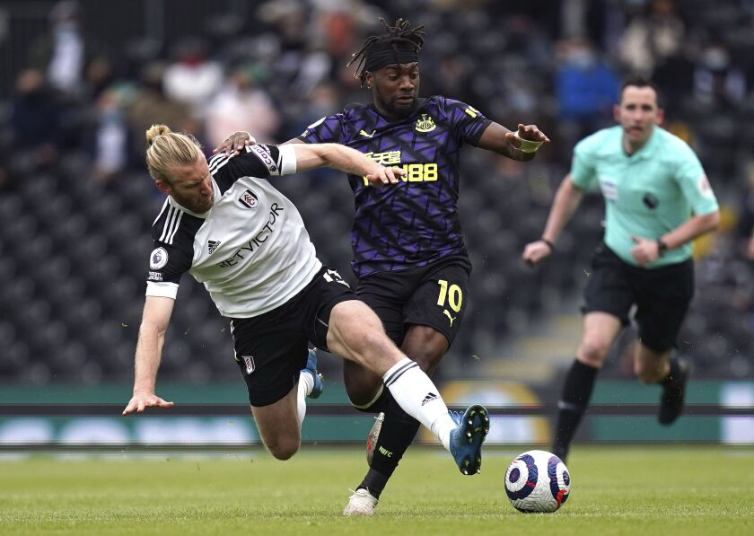 Fulham's Tim Ream, left, and Newcastle United's Allan Saint-Maximin battle for the ball during the English Premier League soccer match at Craven Cottage, London, Sunday May 23, 2021. (Matthew Childs/Pool via AP)