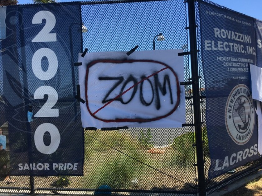 A sign taped to a fence at Newport Harbor High School has the word 'ZOOM' striked out. The Newport-Mesa Unified School District Board of Trustees voted Tuesday to cancel in-person graduations in June.