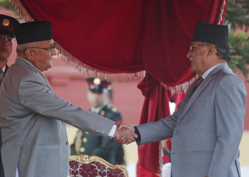 FILE- In this Feb. 15, 2018 file photo, Nepal's Prime Minister Khadga Prasad Oli, left, shakes hand with the chairman of Communist Party of Nepal (Maoist Centre) Pushpa Kamal Dahal after taking the oath of office at the Presidential building in Kathmandu, Nepal. Oli could be forced out of office within weeks amid an internal tussle for power within his governing party following his sharp rhetoric on neighboring India and as Chinese influence grows in Nepal. (AP Photo/Niranjan Shrestha, File)