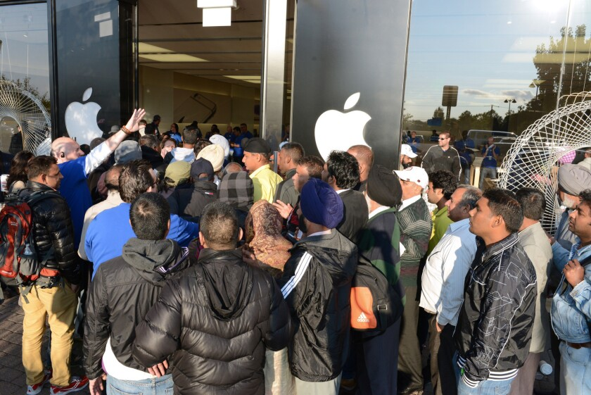 Apple Store employees in Woodcliff Lake, N.J., try and control the crowd as the store opens Friday, the first day of sales for the iPhone 6 and the iPhone 6 Plus.