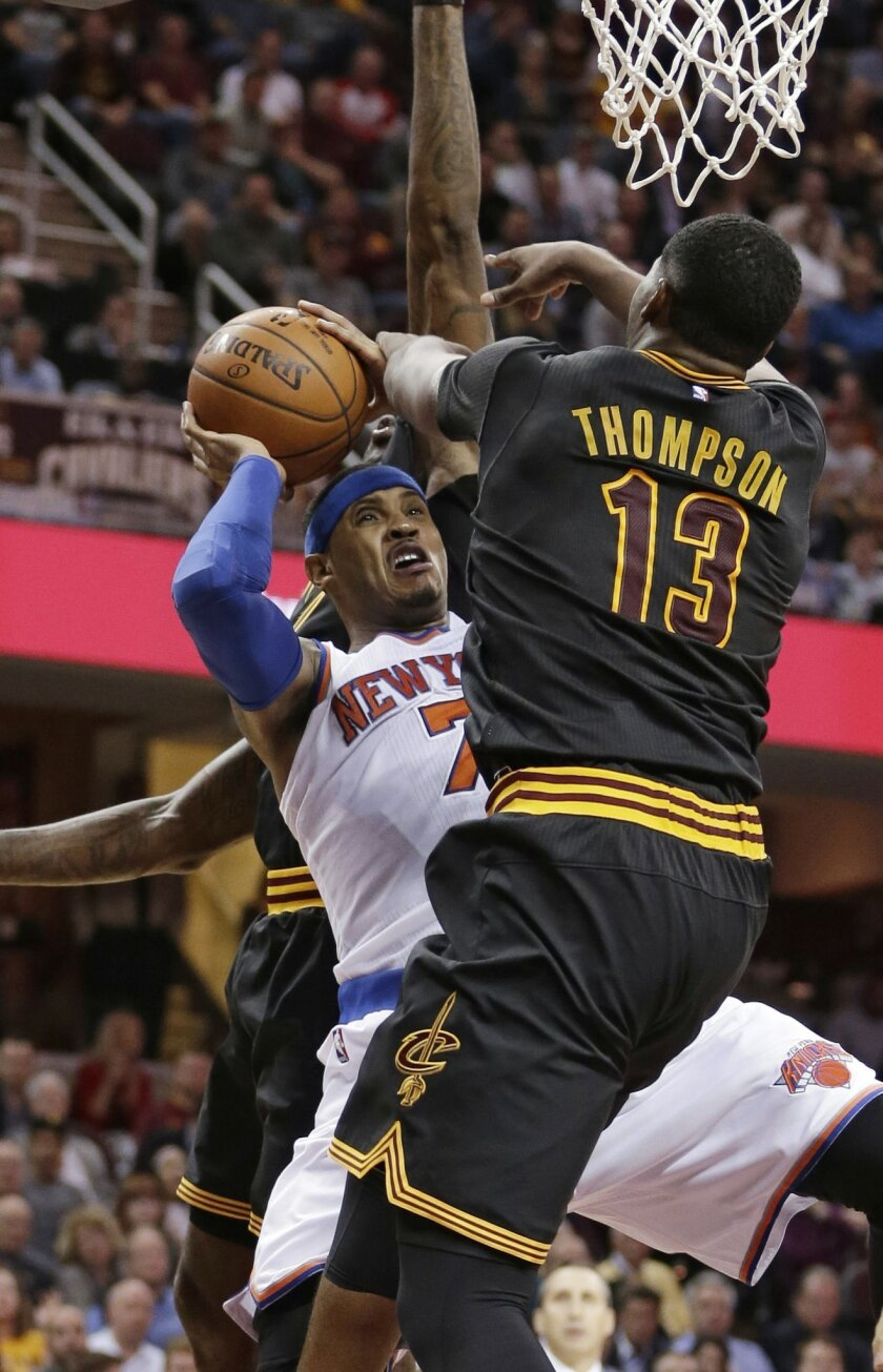 New York Knicks' Carmelo Anthony, center, tries to shoot between Cleveland Cavaliers' LeBron James, back and Tristan Thompson during the second half of an NBA basketball game Wednesday, Nov. 4, 2015, in Cleveland. (AP Photo/Tony Dejak)
