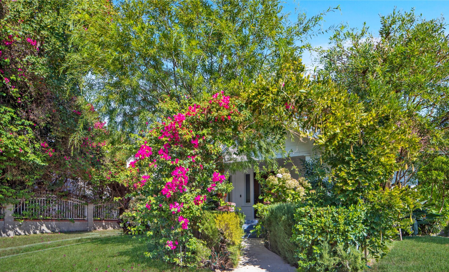 The miniature compound includes a century-old Craftsman, a detached guesthouse and a whimsical backyard with secluded nooks and fruit trees.
