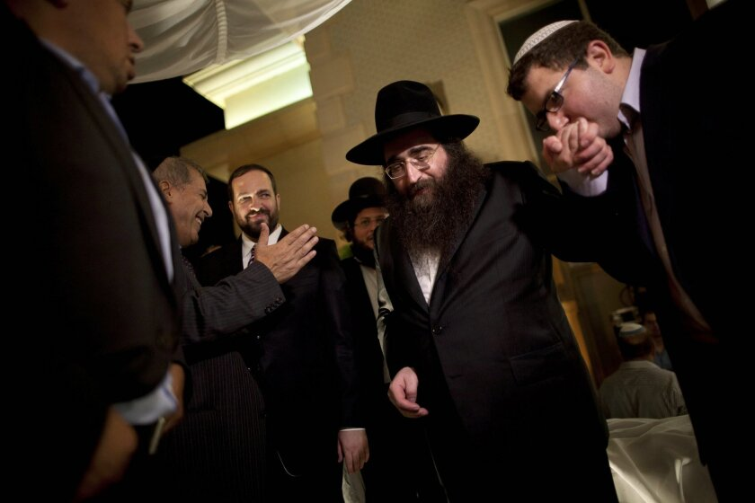 FILE - In this July 11, 2011 file photo, a man kisses the hand of Rabbi Yoshiyahu Pinto at a wedding in Lod, central Israel. An Israeli prison spokeswoman said Pinto, a celebrity rabbi with a following in the United States, has reported to prison on Tuesday, Feb. 16, 2016, to begin a one-year sente
