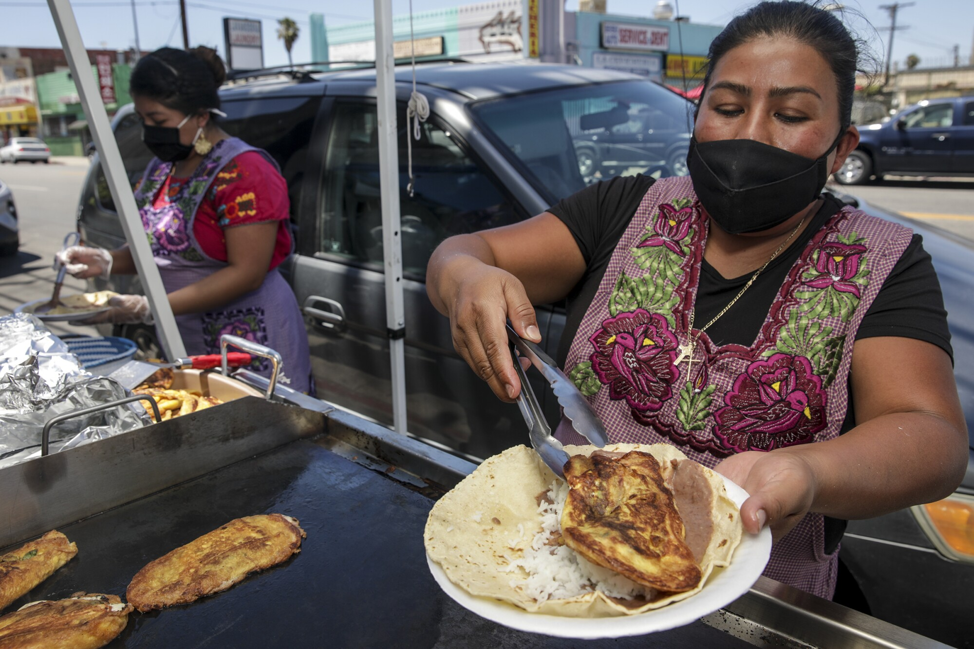 Two woman wearing masks cook outside