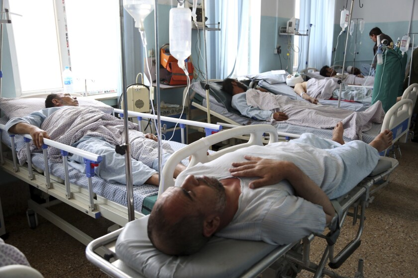 Wounded men receive treatment in a hospital after a bomb blast in Kabul, Afghanistan, Monday, July 1