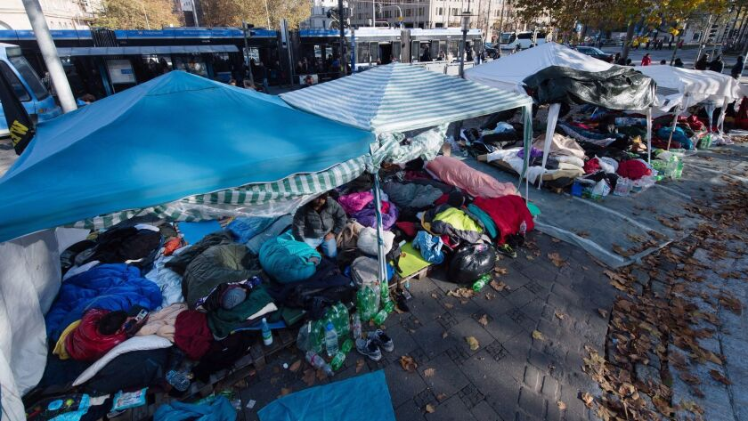 Migrants lie in tents in Munich, Germany, on Friday.