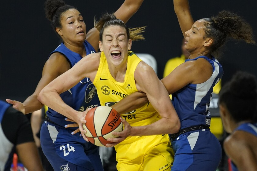 Seattle Storm forward Breanna Stewart (30) gets fouled by Minnesota Lynx forward Mikiah Herbert Harrigan (21) during the second half of Game 3 of a WNBA basketball semifinal round playoff series Sunday, Sept. 27, 2020, in Bradenton, Fla. Looking on is Lynx forward Napheesa Collier (24). (AP Photo/Chris O'Meara)