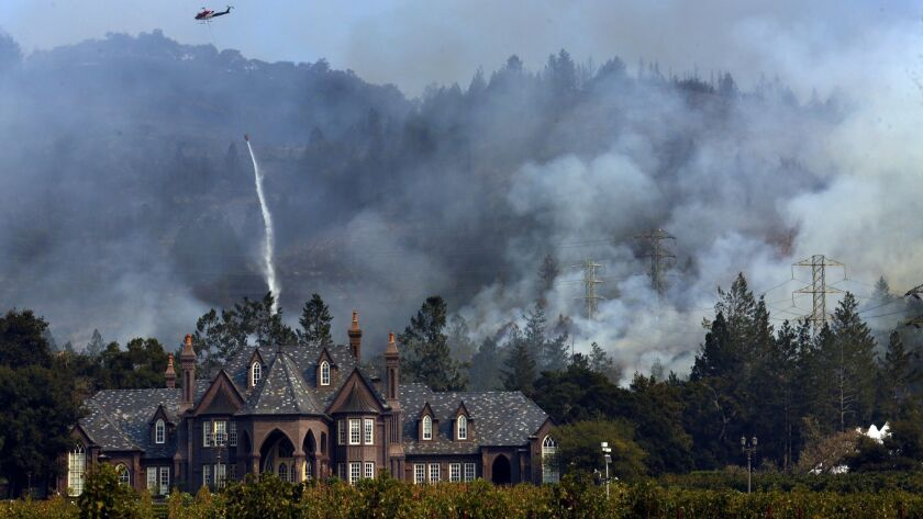 SANTA ROSA, CA -- OCTOBER 14, 2017 -- A helicopter drops water on a fire that threatens the Ledson W