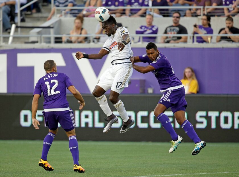 Philadelphia Union's C.J. Sapong (17) heads the ball away from Orlando City 's Kevin Alston (12) and Tommy Redding during the first half of an MLS soccer game, Wednesday, May 25, 2016, in Orlando, Fla. (AP Photo/John Raoux)