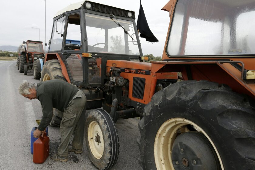 A farmer changes oil in his parked tractor during a protest at a vital point, on a road that links the international airport with the southern and eastern suburbs of the Greek capital, in Koropi, near Athens, Wednesday, Feb. 10, 2016. Farmers in northern Greece blocked traffic on the country's main