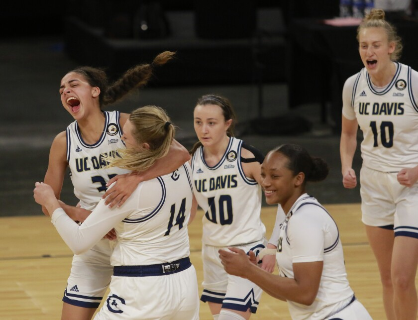 UC Davis' Cierra Hall (32), far left, celebrates with teammate UC Davis' Emma Gibb (14) after they won an NCAA college basketball game against UC Irvine in the championship of the Big West Conference tournament Saturday, March 13, 2021, in Las Vegas. (AP Photo/Ronda Churchill)