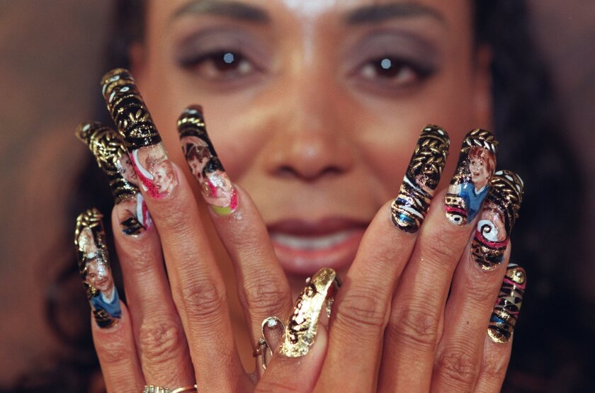 Florence Griffith Joyner displays the finished result of the running scene Phil Roberts paints on her nails.