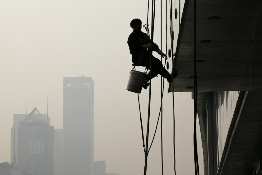 A worker is silhouetted as he cleans a window at a shopping mall in Beijing, China, Wednesday, Nov. 4, 2015. President Xi Jinping said on Tuesday that China needs at least 6.5 percent economic growth in coming years and the Communist Party announced plans to let its tightly controlled yuan trade fr