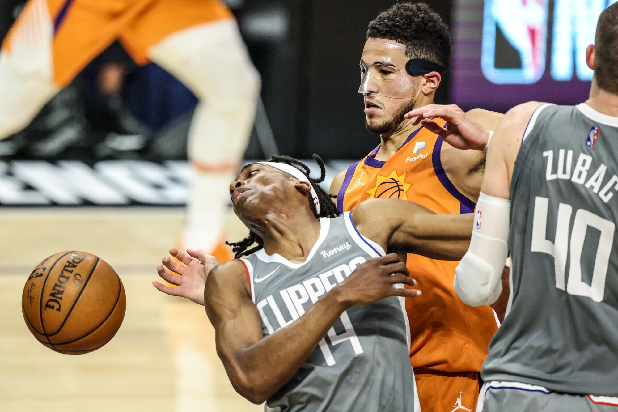 Clippers guard Terance Mann is fouled by Suns guard Devin Booker late in the first half of Game 4.