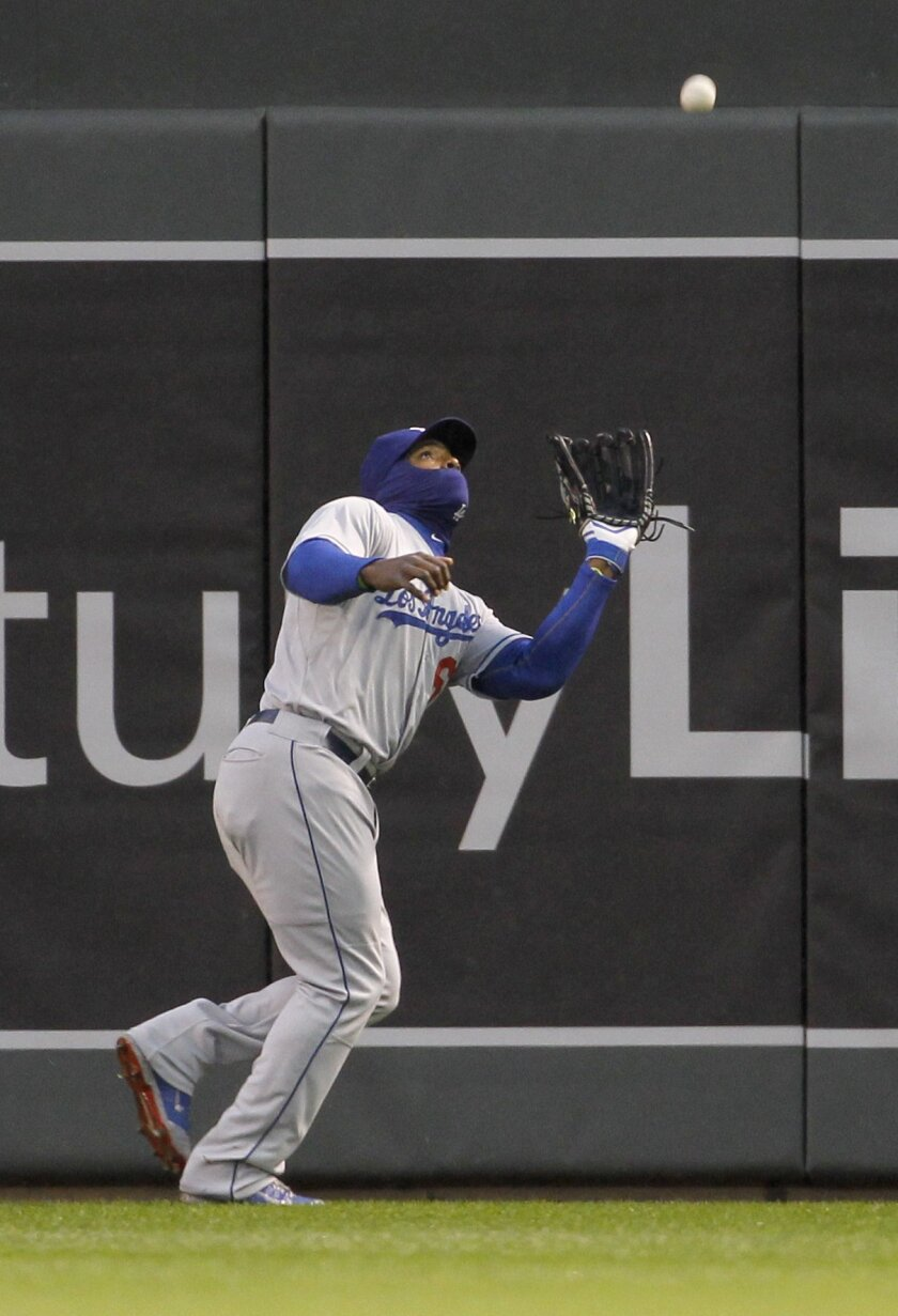 Los Angeles Dodgers right fielder Yasiel Puig catches a fly ball to right field by Minnesota Twins' Brian Dozier during the first inning of a baseball game in Minneapolis, Wednesday, April 30, 2014. (AP Photo/Ann Heisenfelt)