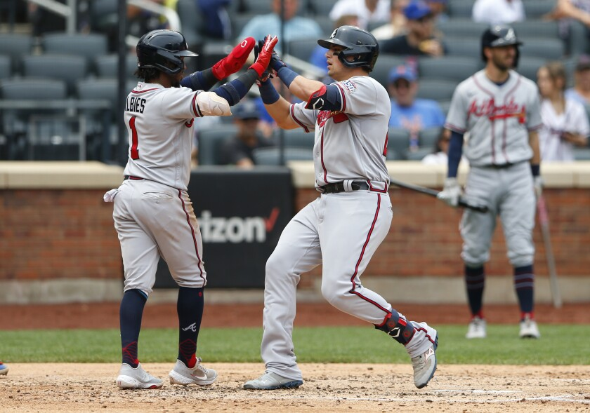 Atlanta Braves Ozzie Albies and Austin Riley celebrate after scoring against the New York Mets during the fourth inning of a baseball game Thursday, July 29, 2021, in New York. (AP Photo/Noah K. Murray)