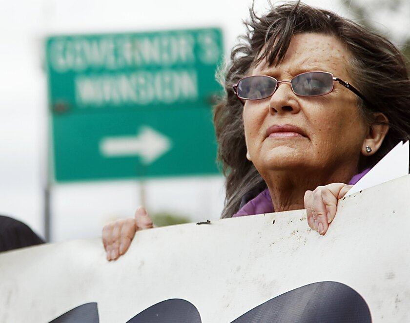 Fannie Bates of Oklahoma City holds a sign urging Gov. Mary Fallin to issue a stay in the execution of two inmates, during a protest Tuesday, April 29, 2014, near the Governor's Mansion in Oklahoma City. A botched execution that used a new drug combination left an Oklahoma inmate writhing and clenching his teeth on the gurney later Tuesday, leading prison officials to halt the proceedings before the inmate's eventual death from a heart attack. (AP Photo/The Oklahoman, KT King)