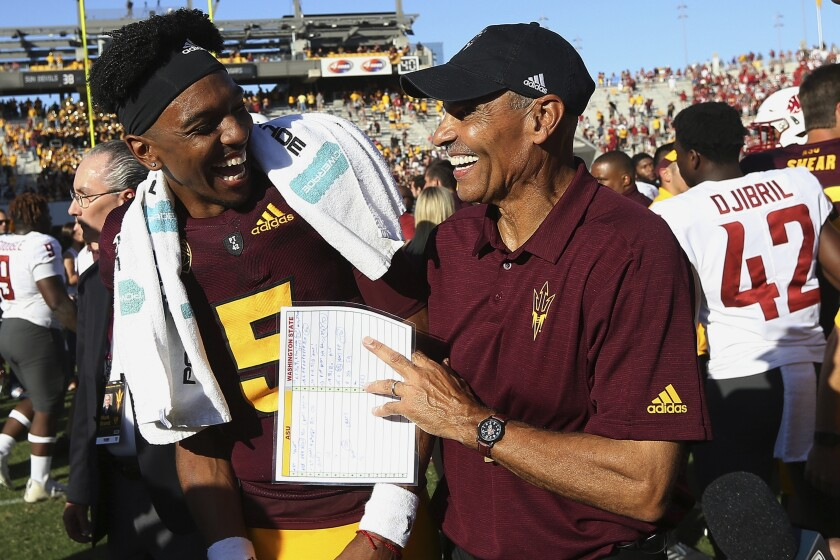 FILE - This Saturday, Oct. 12, 2019, file photo shows Arizona State quarterback Jayden Daniels (5) celebrating with head coach Herm Edwards after an NCAA college football game win over Washington State, in Tempe, Ariz. Arizona State won seven games and played in a bowl game in 2018, exceeding outside expectations in its first season under Edwards, the former NFL player, coach and commentator. The Sun Devils took another step last season, winning eight games and the Sun Bowl. (AP Photo/Ross D. Franklin, File)