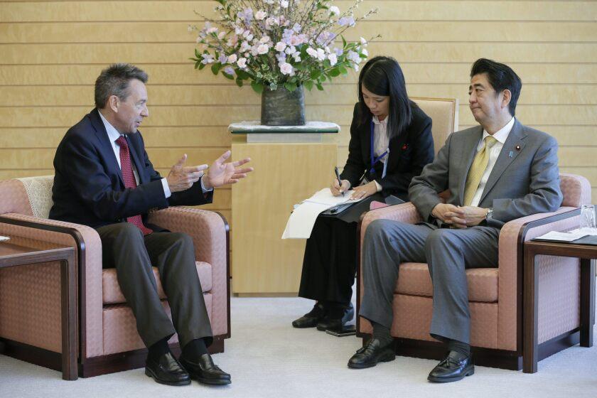 El suizo Peter Maurer (i), presidente del Comité Internacional de la Cruz Roja (CICR), habla con el primer ministro japonés, Shinzo Abe.