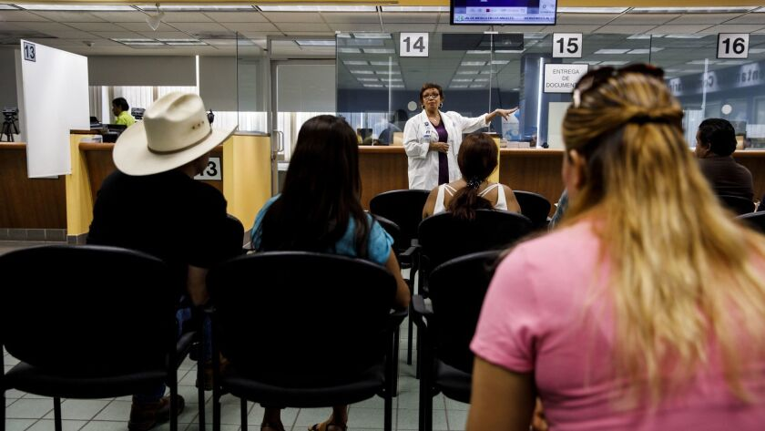 Planned Parenthood Los Angeles nurse practitioner Teresa Arellano, in white lab coat, speaks to people waiting to receive documents about healthcare services and testing available from Planned Parenthood at the Mexican Consulate General in Los Angeles.