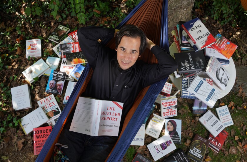 """Carlos Lozada with some of the 150 books he read for his metahistory, """"What Were We Thinking."""""""
