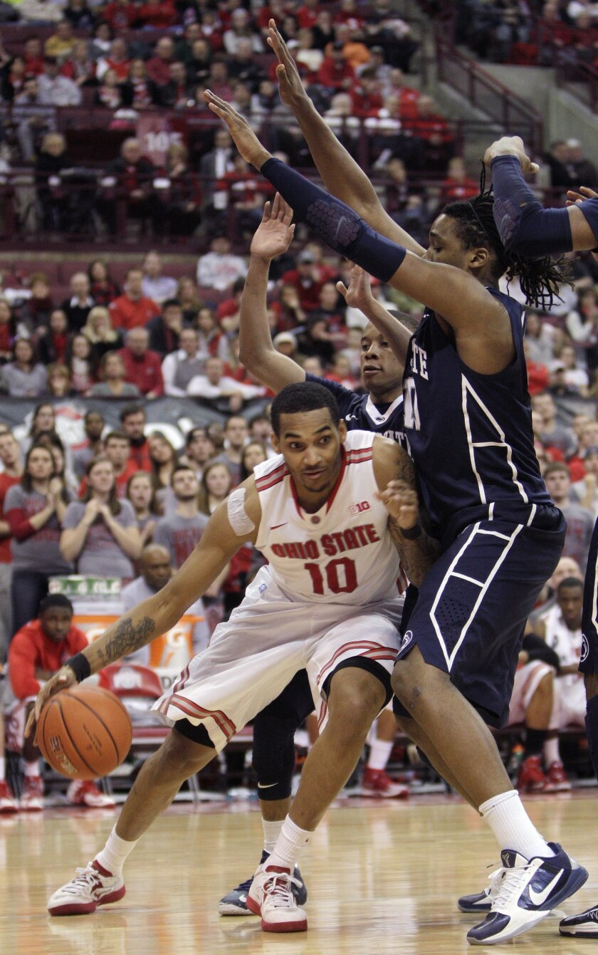 Ohio State's LaQuinton Ross, left, drives the baseline against Penn State's Tim Frazier, center, and Brandon Taylor during the second half of an NCAA college basketball game Wednesday, Jan. 29, 2014, in Columbus, Ohio. Penn State beat Ohio State 71-70 in overtime. (AP Photo/Jay LaPrete)