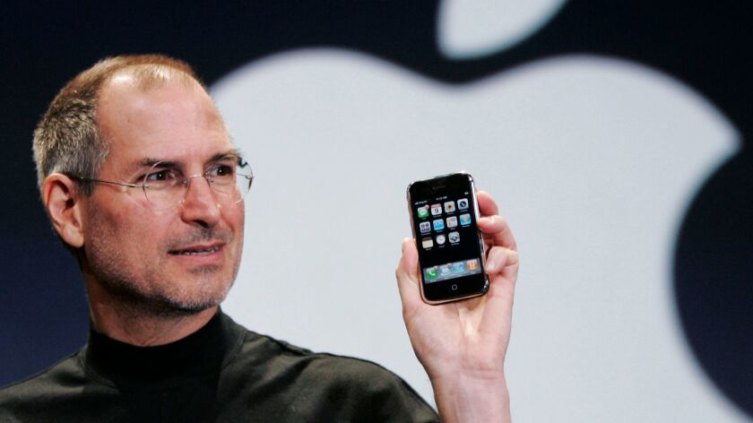 FILE- In this Jan. 9, 2007, file photo, Apple CEO Steve Jobs holds up an iPhone at the MacWorld Conf