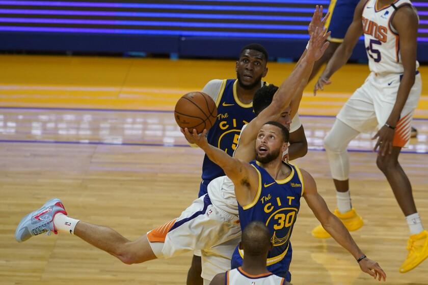 El jugador de los Warriors de Golden State Stephen Curry (con el 30) lanza la pelota en un partido contra los Suns de Phoenix junto al jugador de los Suns Devin Booker, el la segunda mitad de su juego de NBA en San Francisco, el martes 11 de mayo de 2021. (AP Foto/Jeff Chiu)