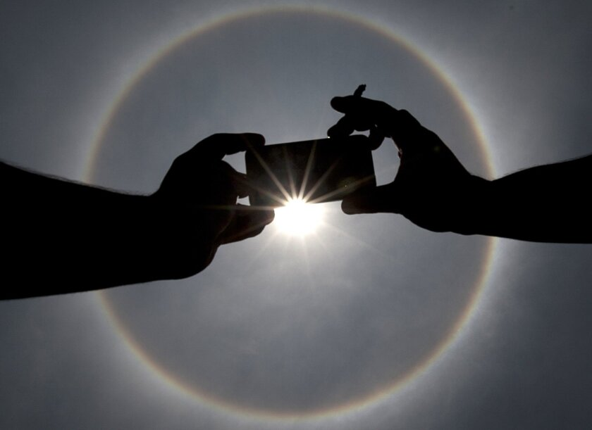 In this Thursday, May 21, 2015 photo, a man uses his mobile phone to photograph a circular sun halo in Mexico City. The ring around the sun is a fairly common weather phenomenon caused by ice crystals in the upper atmosphere. (AP Photo/Marco Ugarte)