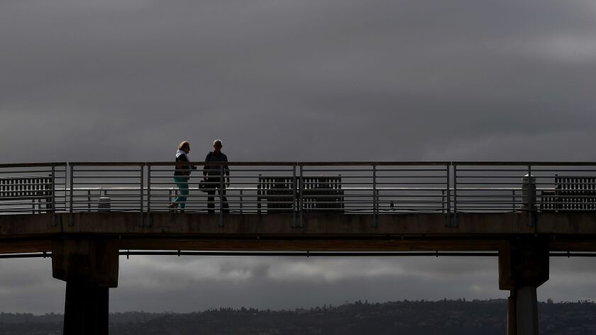 People walk along the Hermosa Beach Pier as clouds linger after morning rain dampened the Southland.