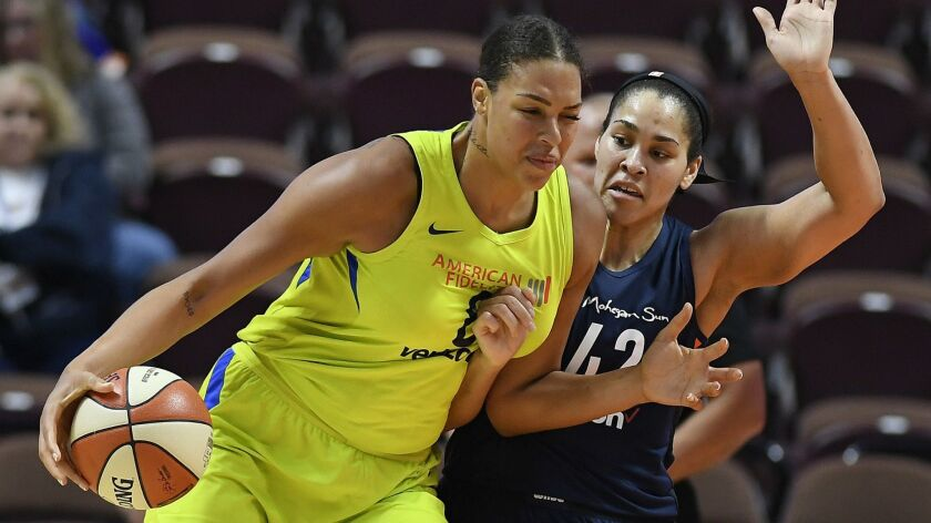 FILE - In this May 8, 2018, file photo, Dallas Wings' Liz Cambage, left, drives against Connecticut