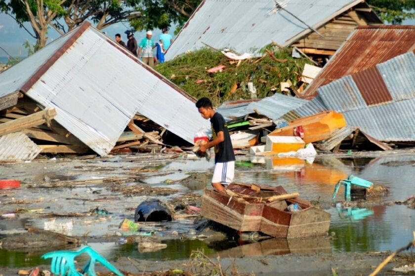 A man surveys the damage caused by earthquake and tsunami in Palu, Central Sulawesi, Indonesia, Saturday, Sept. 29, 2018.