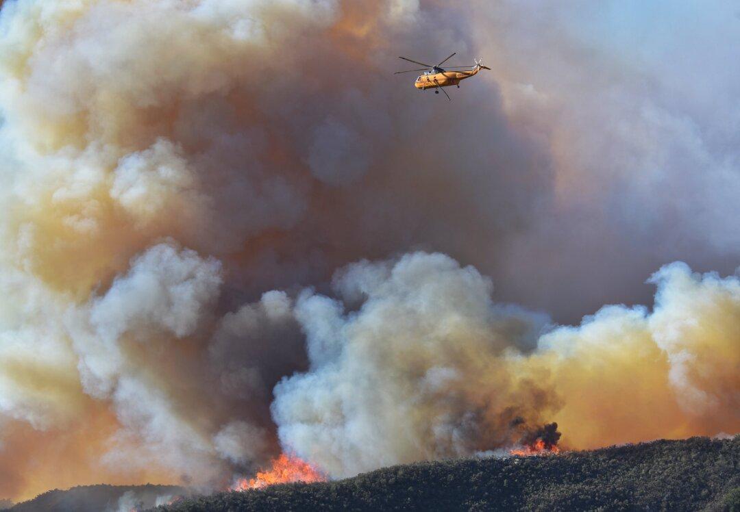 A helicopter flies through smoke.