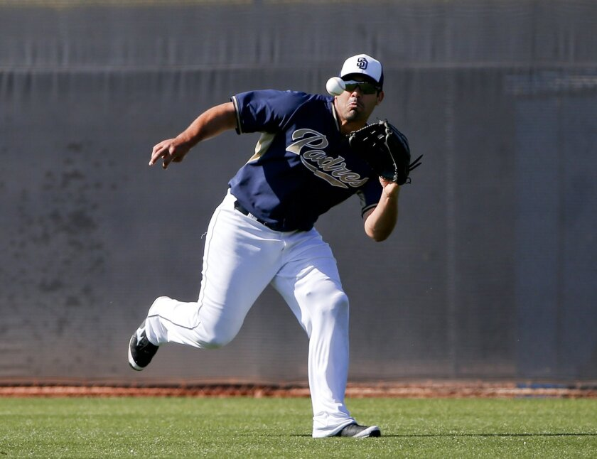 FILE- In this March 23, 2015, file photo, San Diego Padres left fielder Carlos Quentin runs down a line drive during fielding drills for outfielders prior to a spring training baseball game against the Chicago White Sox in Peoria, Ariz.  Quentin retired Friday, May 1, 2015,  after chronic knee inju