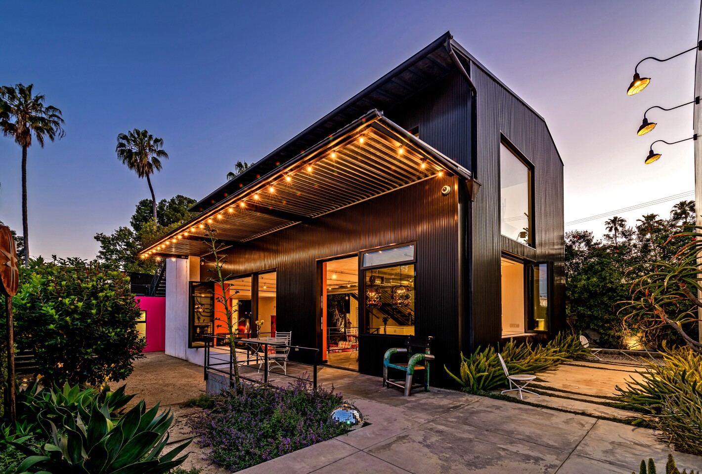The unusual Venice compound, created for a toy company executive, evokes an urban warehouse with its metal siding and outdoor staircases that resemble fire escapes. Inside, polished concrete floors and exposed ductwork pair with artistic fixtures and splashes of color. Listed for $8.25 million, the fenced and hedged property includes a three-bedroom main house and a 430-square-foot studio. The backyard patio was inspired by the loading dock at Santa Monica's Bergamot Station. Two rooftop decks and a fire pit are among other outdoor features. A pixelated art piece by French street artist Invader, believed to be the artist's first residential commission, adorns a side of the of the warehouse-like design.