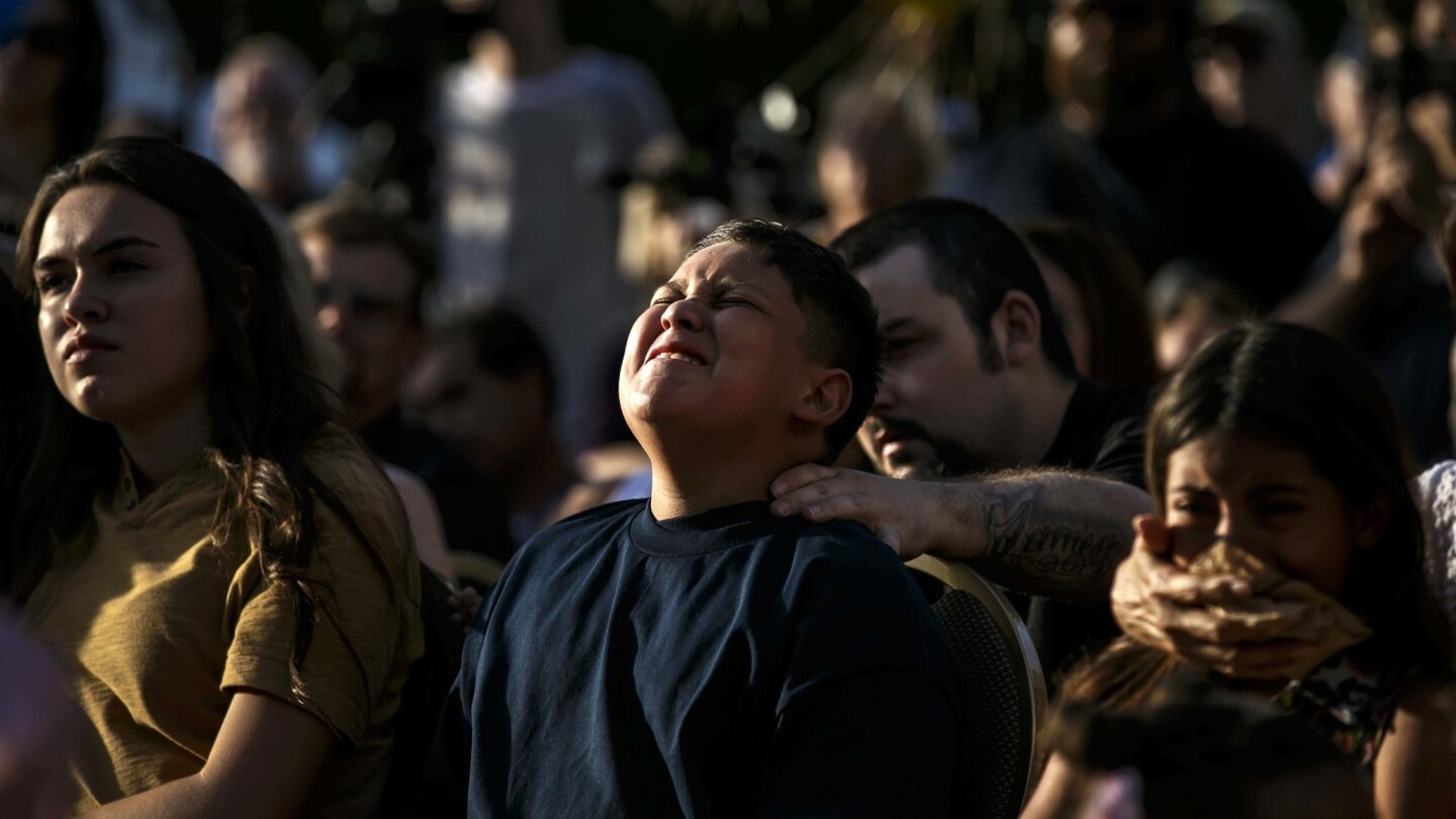 """James Carter, 11, grandson of Officer Jose """"Gil"""" Vega, is comforted by family members during a vigil for the slain Palm Spring police officers."""