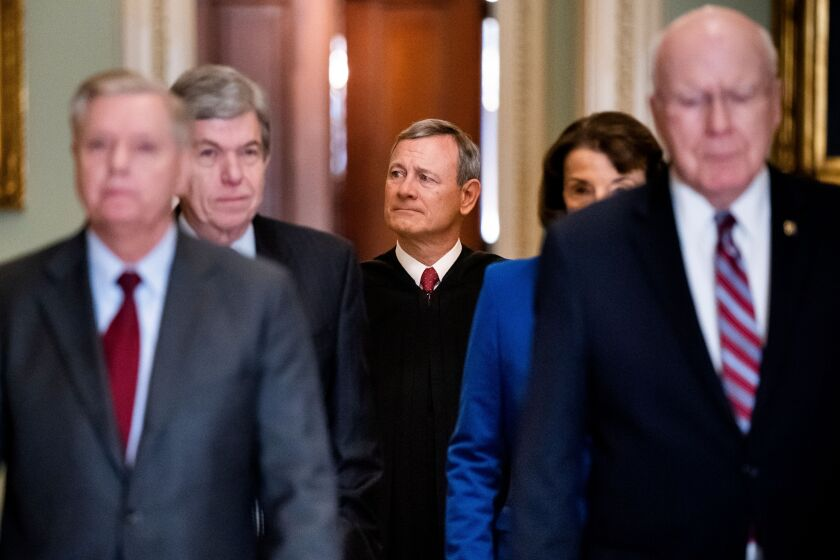 Chief Justice John G. Roberts Jr., center, arrives at the Senate to swear in lawmakers for President Trump's impeachment trial.