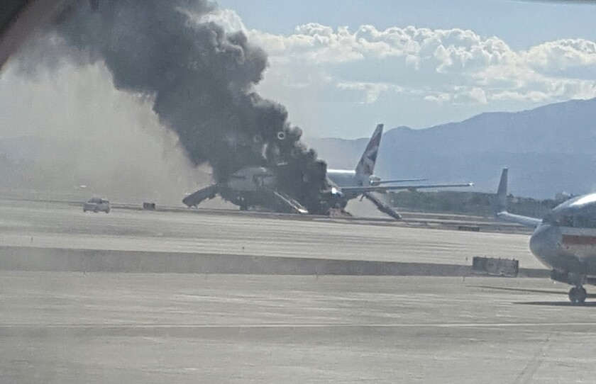 In this photo taken from another plane window, smoke billows from an aircraft that caught fire at McCarren International Airport in Las Vegas.
