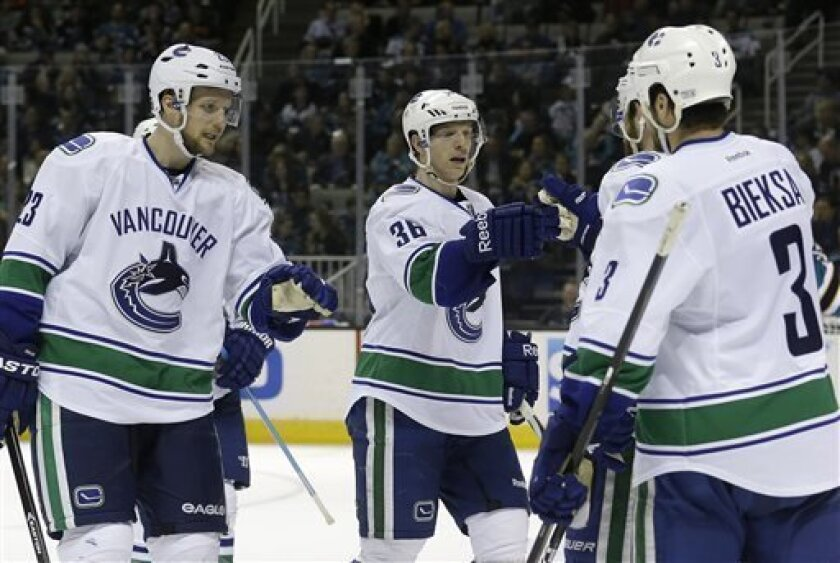 Vancouver Canucks defenseman Alexander Edler (23), from Sweden, right wing Jannik Hansen (36), from Denmark, and defenseman Kevin Bieksa (3) congratulate left wing Chris Higgins, hidden, after scoring during the second period of an NHL hockey game against the San Jose Sharks in San Jose, Calif., Mo