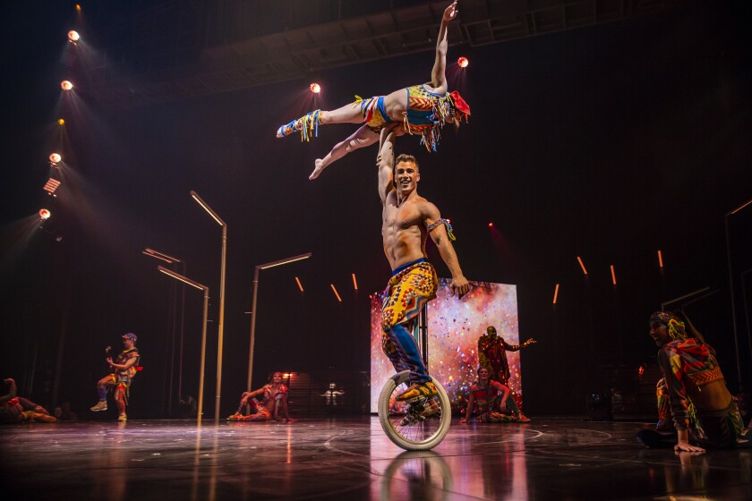 A man on a unicycle holds a performer above his head using one arm.