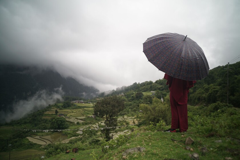 """A young monk with an umbrella overlooks his Himalayan village in the documentary """"Sing Me a Song."""""""